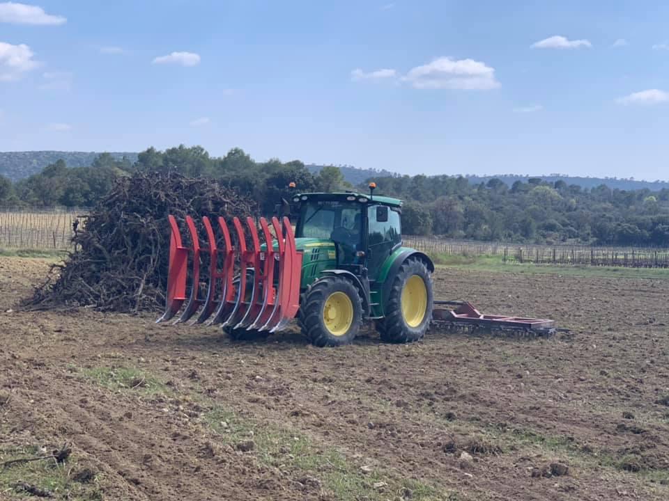 Tracteur équipé d'une herse et d'une grille